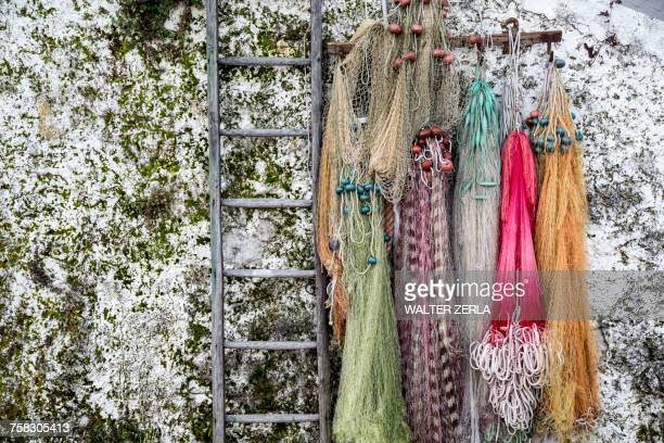 fishing nets hanging from wall at isola pescatori, lake maggiore piedmont, italy - stresa stock pictures, royalty-free photos & images