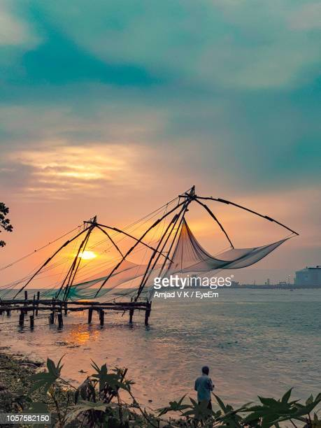 fishing nets in sea against sky during sunset - kochi india stock pictures, royalty-free photos & images