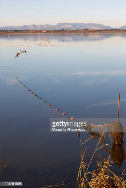 Fishing nets on calm lake waters and mountains at the background