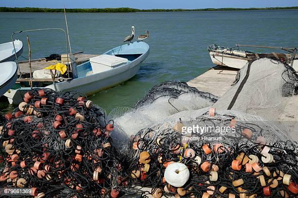fishing nets on pier; boats and ocean beyond - timothy hearsum stock-fotos und bilder