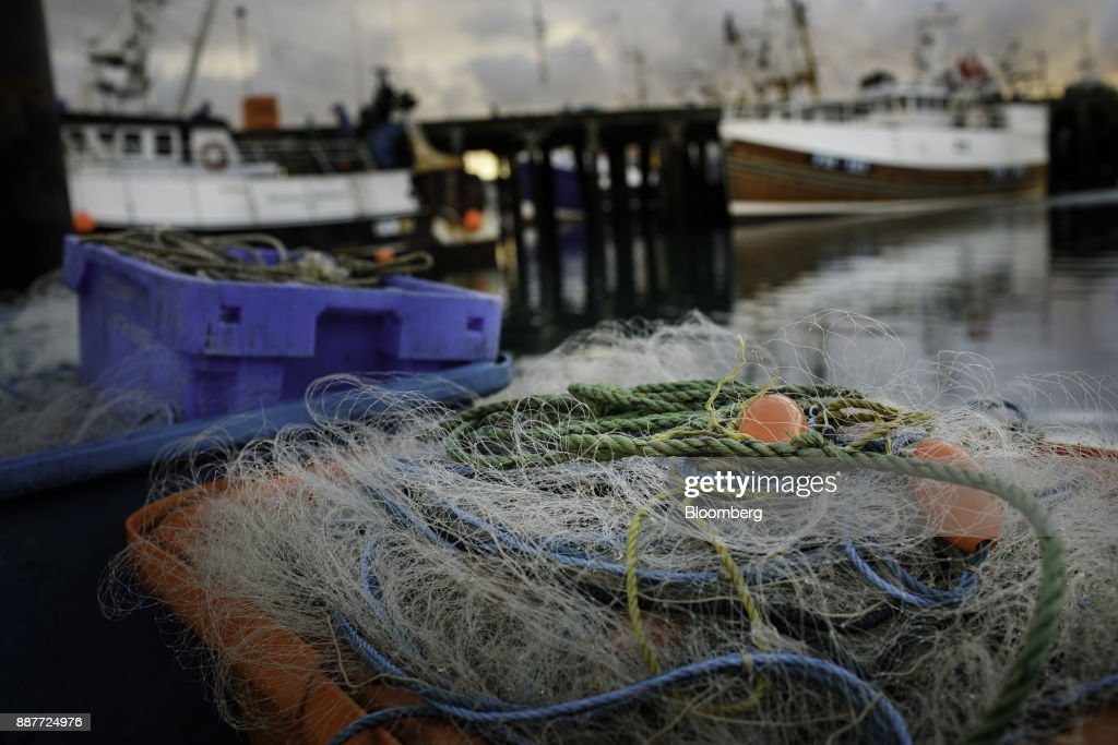 Fishing nets sit in containers on the dockside near fishing vessels at moorings in Newlyn, U.K., on Wednesday, Nov. 29, 2017. Prime Minister Theresa May will pull Britain out of the 1964 London convention that allows European fishing vessels to access waters as close as six to twelve nautical miles from the U.K. coastline. Photographer: Annie Sakkab/Bloomberg via Getty Images