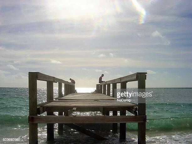 fishing off pier in bahamas - grand bahama stock photos and pictures