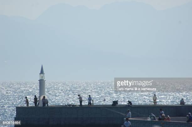 fishing on breakwater - 防波堤 ストックフォトと画像