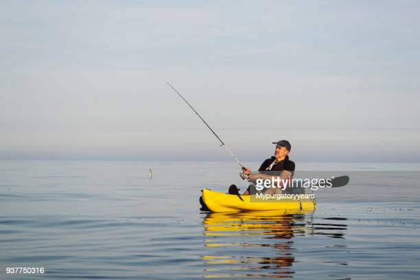 fishing on calm and sunny seas - kayak stock pictures, royalty-free photos & images