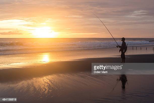 Fishing on the beach at sunset in bali Indonesia