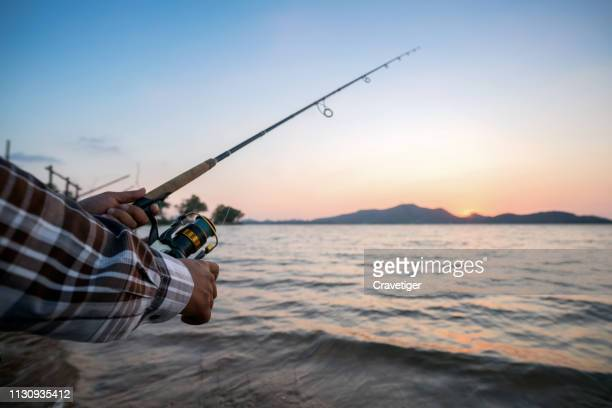 fishing on the lake on a sunny day. hands and fishing rod of the fisherman macro. fishing rod and hands of the fisherman over the lake water - 淡水釣り ストックフォトと画像