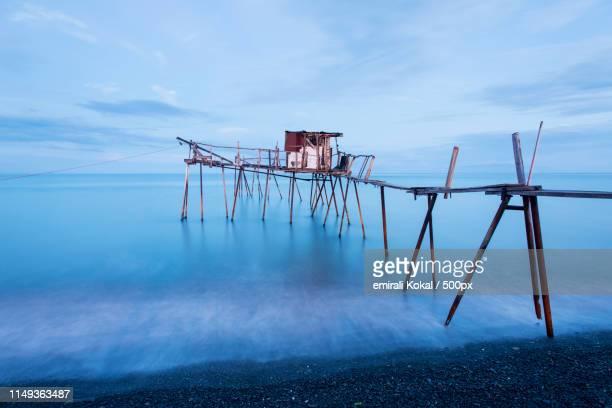 fishing pier and smooth ocean at sunrise, old wood pier - テキルダー ストックフォトと画像