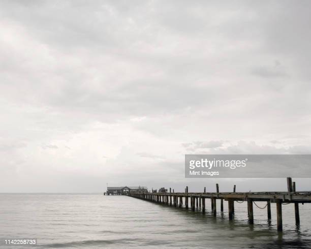 fishing pier - overcast stock pictures, royalty-free photos & images