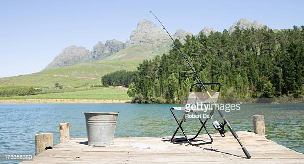 ジョンフィッシング極と椅子がデッキ - 桟橋 ストックフォトと画像