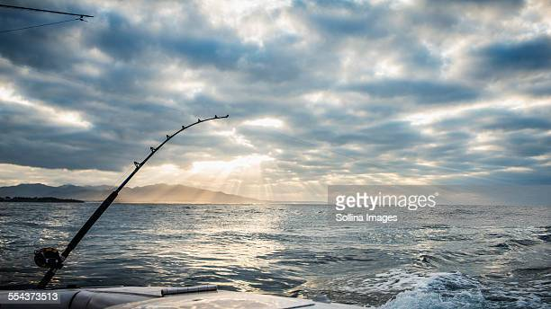 Fishing poles on boat over ocean waves