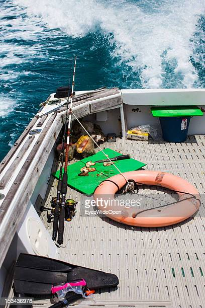 Fishing rod, a life belt, snorkeling gear and fresh catched conchs on a boat on June 15, 2012 in Long Island, The Bahamas.