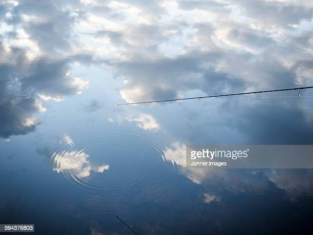 fishing rod and clouds reflecting in water - dalsland stock photos and pictures