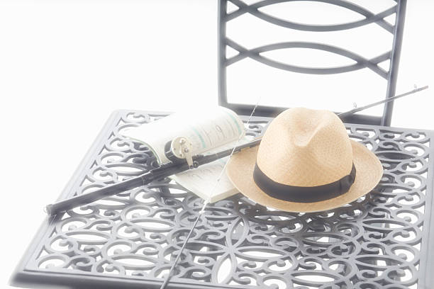 Fishing rod, book and hat on wrought iron table