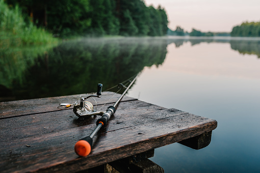Fishing rod, spinning reel on the background pier river bank. Sunrise. Fog against the backdrop of lake. Misty morning. wild nature. The concept of rural getaway. Article about fishing day. 1094918172
