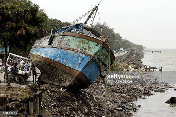 A fishing ship lies on a road near Nagapattinam port some 350 km south of Madras 27 December 2004 after tidal waves hit the region Survivors grimly...