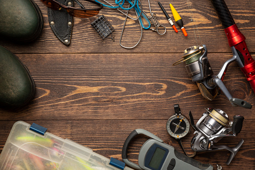 Fishing theme. Frame with rubber boots, fishing box, reels, fishing buoy, rod, compass, feeder, knife and fish string on wooden background. Free space 1143056523