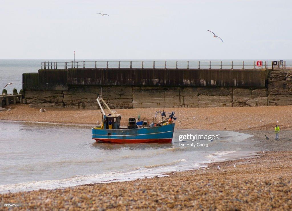 Fishing trawler coming onto beach : Stock Photo