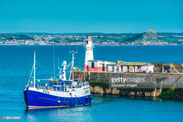 A fishing trawler returning with its catch to the harbor at Newlyn fishing village near Penzance in Cornwall with St Michael's on the horizon UK