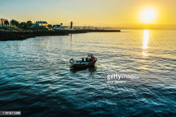 fishing vessel in the sunset. - fishing boat stock pictures, royalty-free photos & images