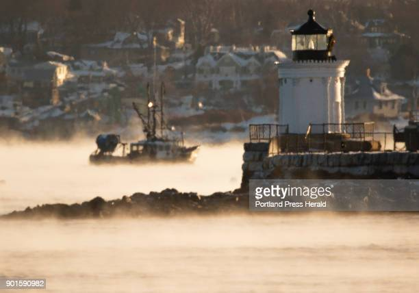 A fishing vessel motors through sea smoke past Bug Light in South Portland on Wednesday morning December 27 2017 An Arctic chill has descended upon...
