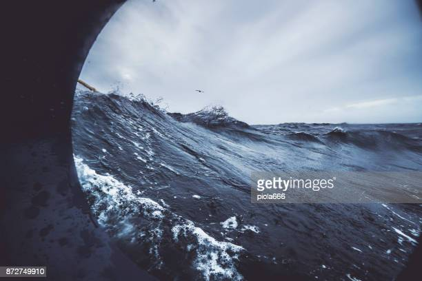 fishingboat vessel fishing in a rough sea - slave ship stock photos and pictures