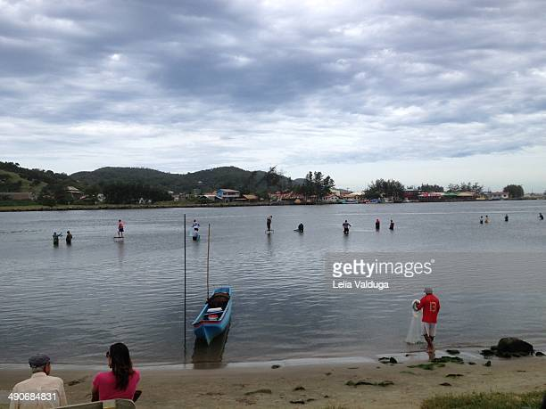 Fishmen, audience, boats and nets on the beach in Laguna, Santa Catarina, Brazil. It's time to go fishing in Laguna and tourists crowd to see the...