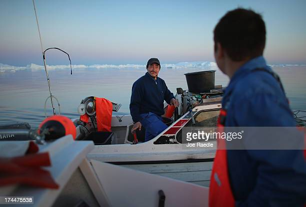 Fishmen gather to chat as they work near icebergs that broke off from the Jakobshavn Glacier on July 23, 2013 in Ilulissat, Greenland. As the sea...