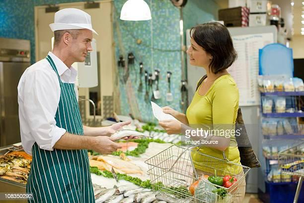 Fishmonger y cliente en supermercado