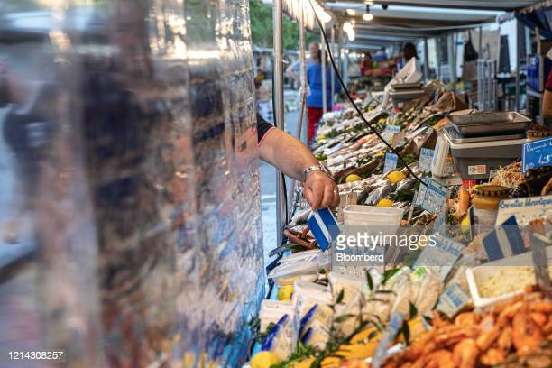 A fishmonger arranges a seafood display behind protective plastic customer facing screens while setting up for business at Marche SaxeBreteuil in...
