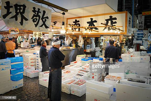 A fishmonger arranges his stall at the famous Tsukiji fish market where tuna auctions are suspended during the earthquake crisis period in downtown...