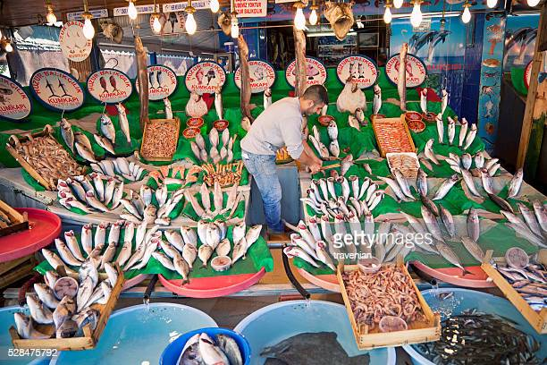 Fishmonger arranging fishes on table