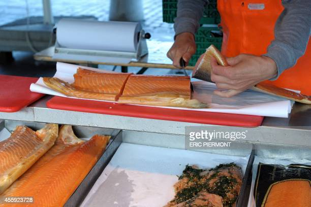 Fishmonger cut salmons and other fishes at the Fish Market near the Norwegian harbor of Bergen on September 12, 2014 in Bergen. AFP PHOTO ERIC...