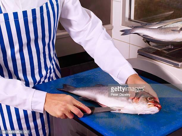 Fishmonger filleting sea bass fish
