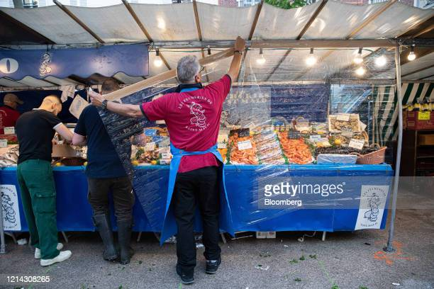 A fishmonger hangs protective plastic customer facing screens while setting up his seafood stall for business at Marche SaxeBreteuil in Paris France...