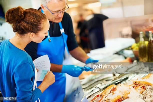 Fishmonger ayudar a un cliente