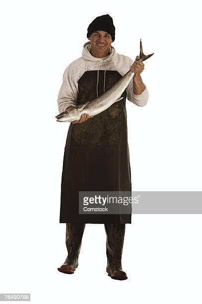 Fishmonger holding a fish