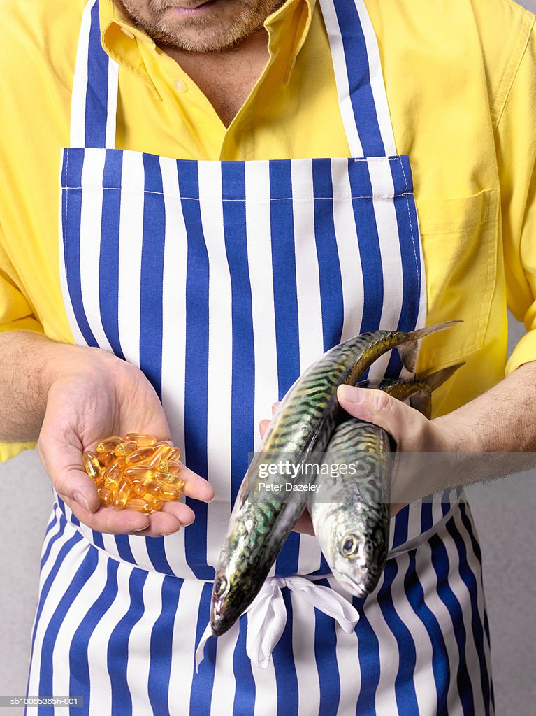Fishmonger holding mackerel and Cod Liver oil tablets, close-up, mid section : Foto stock