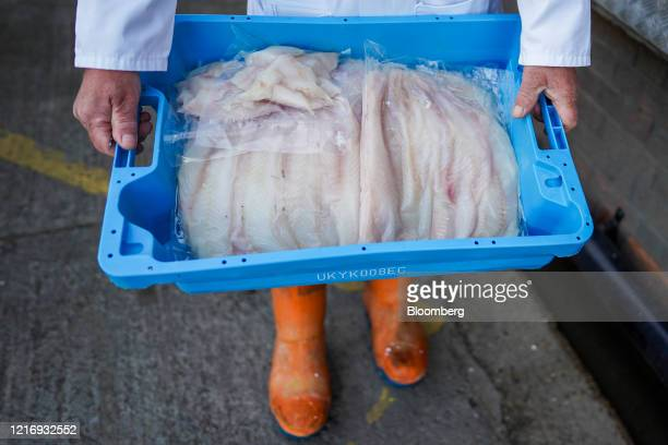 A fishmonger holds a box of Haddock fillets in Scarborough UK on Tuesday June 2 2020 The threat of a nodeal Brexit is back and with it the risk that...
