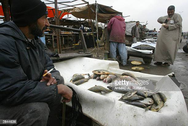 A fishmonger prepares fish at a market in Baghdad's predominantly Shiite Muslim neighborhood of Sadr City 05 January 2004 Iraq's capital a city which...