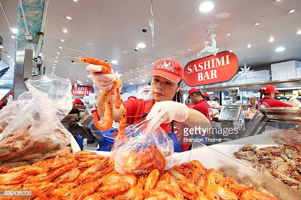 A fishmonger prepares prawns for customers at the Sydney Fish Market on December 23 2016 in Sydney Australia The Sydney Fish Markets experiences its...