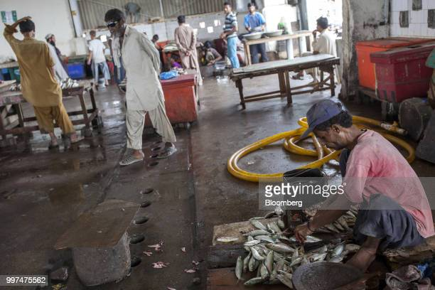 A fishmonger scales a fish in a market at the harbor in Gwadar Balochistan Pakistan on Tuesday July 4 2018 What used to be a small fishing town on...