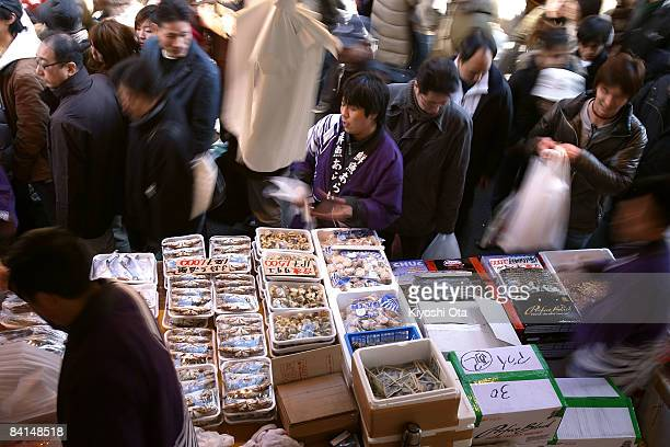 A fishmonger sells seafood at a fish stall in the Ameya Yokocho street market on December 31 2008 in Tokyo Japan People shop around in preparation to...