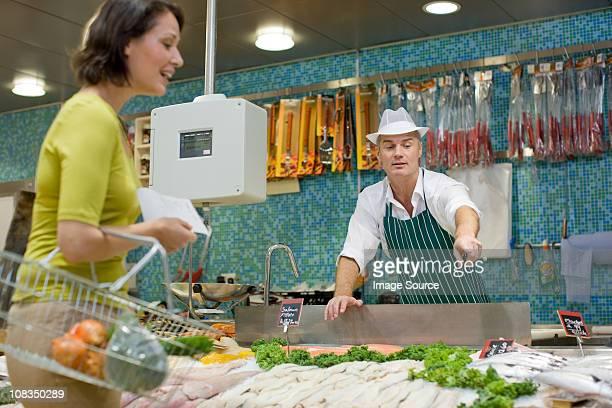 Fishmonger hablando con el cliente en el supermercado