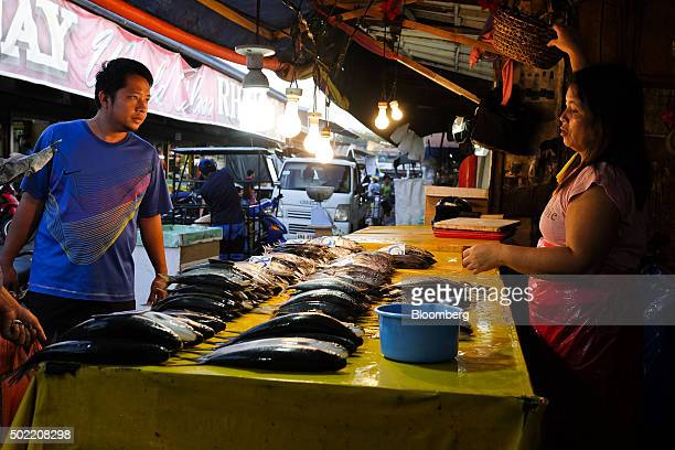 A fishmonger talks to a customer at a market stall in Davao Mindanao the Philippines on Saturday Dec 12 2015 Davao city's reputation as one of the...