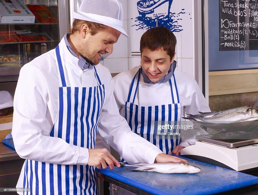 Fishmonger teaching trainee how to fillet Sea bass fish : Foto de stock