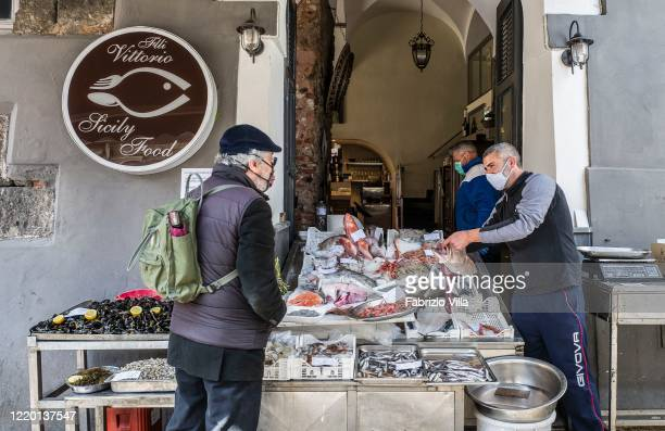 A fishmonger wearing a face mask works at his shop after reopening following the ministerial decree that allowed the resumption of certain activities...