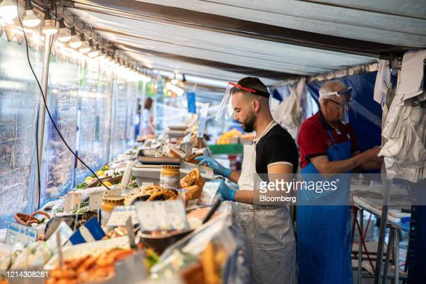 A fishmonger weighs seafood behind protective plastic customer facing screens at Marche SaxeBreteuil in Paris France on Thursday May 21 2020...