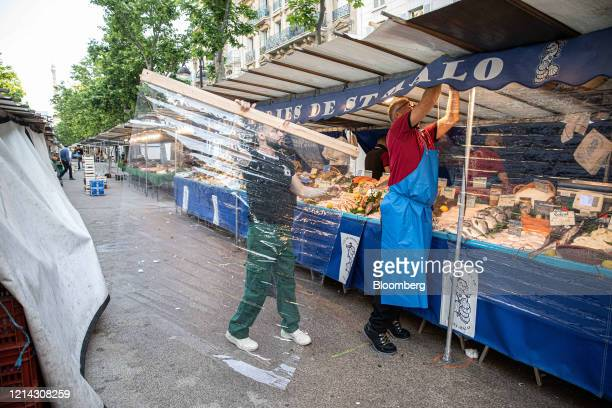 Fishmongers hang protective plastic customer facing screens while setting up a seafood stall for business at Marche SaxeBreteuil in Paris France on...