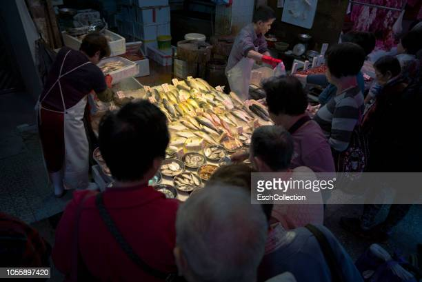Fishmongers market stall with customers in Hong Kong
