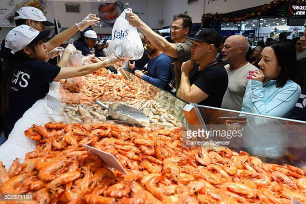 Fishmongers serve customers before Christmas at the Sydney Fish Market on December 24 2015 in Sydney Australia The Sydney Fish Markets experience its...